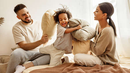 happy family multiethnic mother, father and son laughing, playing, fights pillows and jumping in bed in bedroom at home