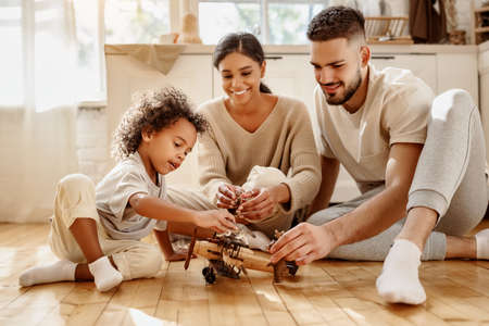 Happy multiethnic family parents and boy playing with toy plane on floor in cozy kitchen at home Banco de Imagens