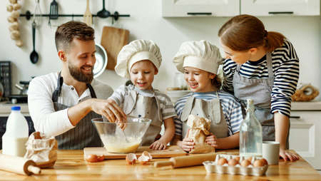 Happy young family with kids gathering in kitchen and preparing dough for pastry while spending weekend together at home
