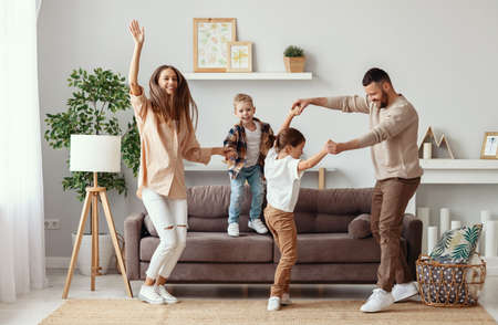 happy family mother father and kids daughter and son dancing and having fun at home Standard-Bild