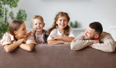 happy family mother father and children at home on the couch