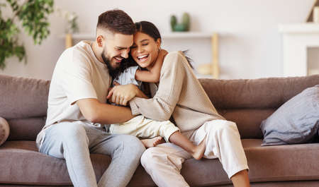 happy multiethnic family mother father and son having fun at home on the couch 版權商用圖片