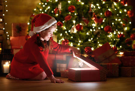 happy laughing child girl with magic gift sitting in front of Christmas tree on Christmas Eve