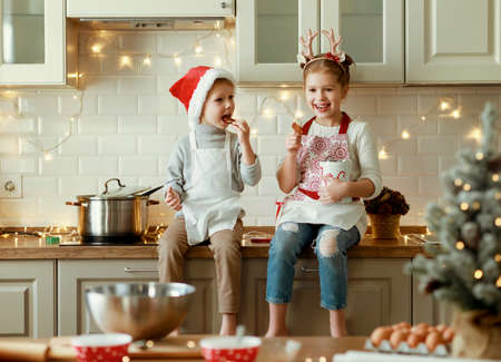 happy funny kids on Christmas eve, girl and boy laugh and eat cookies that they baked together in cozy kitchen at home
