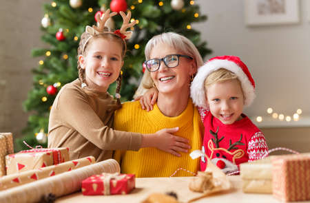 happy family grandmother and grandkids hug and smile for camera while wrapping Christmas gifts in cozy room with Christmas tree