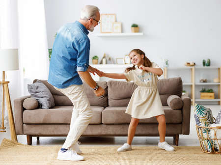 Happy family: girl smiling and dancing with aged grandfather while standing on sofa in cozy living room at home