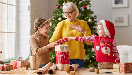 happy family: smiling grandmother and funny grandchildren laughing and together wrapped present while standing in cozy room with Christmas tree 版權商用圖片