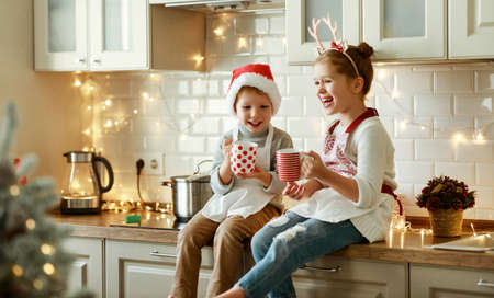 happy funny kids on Christmas eve, girl and boy laugh and drink hot cocoa drink that they baked together in cozy kitchen at home 版權商用圖片