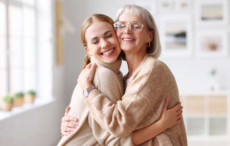 Delighted adult and senior women smiling with closed eyes and hugging each other on weekend day at home