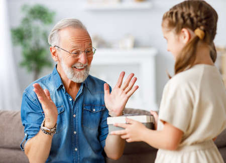 Cheerful elderly male smiling and gesticulating while receiving surprise gift from granddaughter during holiday celebration at home 版權商用圖片
