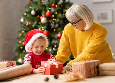 Excited kid in Santa hat opening gift box from granny while celebrating Christmas holiday at home