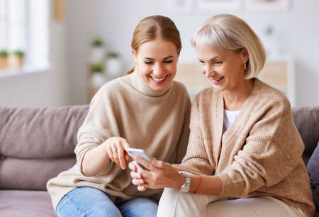 Delighted adult and aged women smiling and browsing social media on smartphone while resting on couch at home together