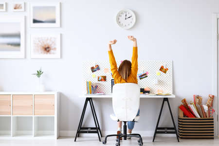 Back view of anonymous woman stretching arms during break in work while sitting at desk in home office