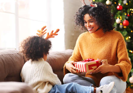 Happy ethnic african american family on holiday: cheerful mother gives a gift to her cute little son during the Christmas celebration in a cozy room with tree Banque d'images