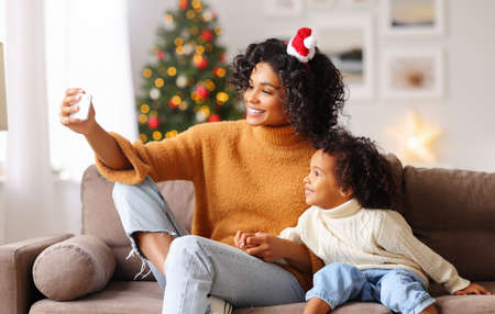 Happy ethnic african american family on holiday: happy mother taking selfie with child congratulating each other at Christmas in a cozy room at home
