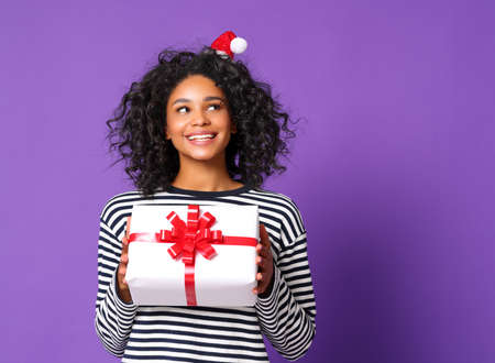 Happy ethnic woman with small Santa hat holding present box and looking away on Christmas day against violet background