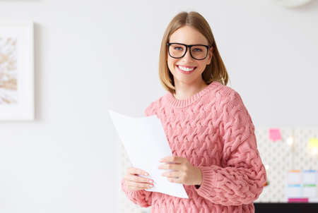 Cheerful young woman in sweater and glasses smiling while doing paperwork in cozy workplace at home
