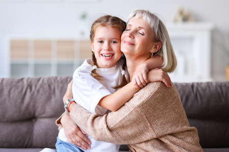 Delighted aged woman and cheerful girl embracing each other and looking at camera while sitting on sofa on weekend day at home