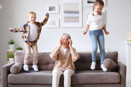Annoying children jumping on sofa and irritating unrecognizable exhausted woman touching head and suffering from headache