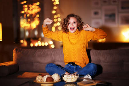 Happy woman raising fist and screaming while watching sports match on couch in evening at home