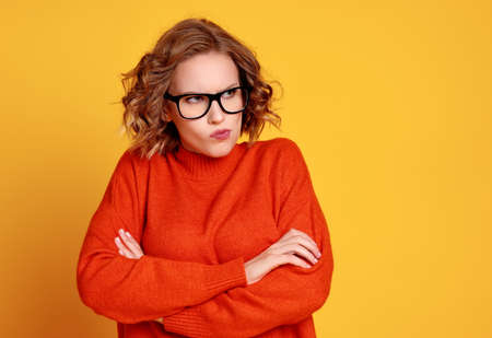 Resentful young female in red sweater and glasses crossing arms and pouting lips while looking away against yellow background