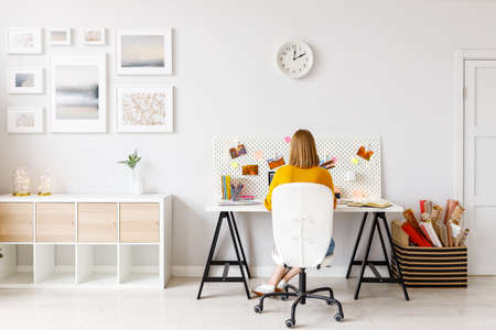 Back view of anonymous woman during work while sitting at desk in home office
