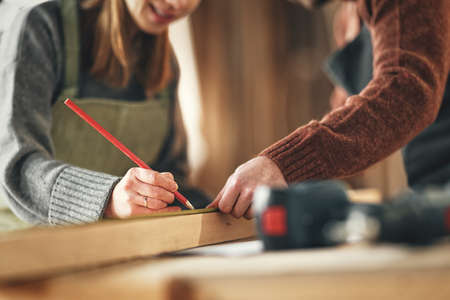 Crop unrecognizable craftswoman making marks on wooden detail while working with anonymous colleague in carpentry workshop