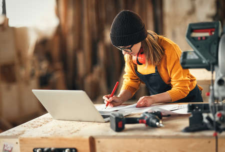 Focused young skilled craftswoman making notes in papers while standing at table with laptop and carpentry instruments in workshop
