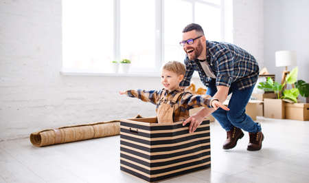 Side view of delighted father riding smiling child in box while having fun during relocation in new flat