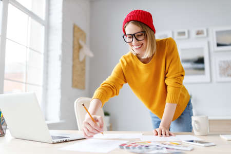 Cheerful female designer in stylish outfit and glasses smiling and drawing sketch leaning on the table during work on remote project at home