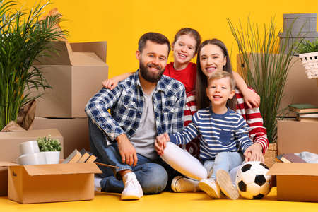 Happy young family: parents with son and daughter sitting together among carton boxes with belongings and looking at camera while moving in new apartment