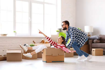Full body side view of positive family couple young man pushing carton box with laughing woman while having fun together during unpacking things in new home 版權商用圖片
