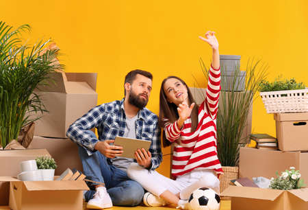 Positive young woman and man with tablet sitting among boxes with belongings and planning interior of new house while preparing for relocation 版權商用圖片