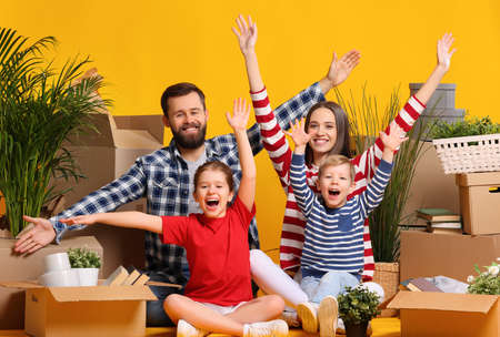 Delighted family: parents and kids having fun and raising arms while sitting together among boxes with belongings after relocation into new apartment 版權商用圖片