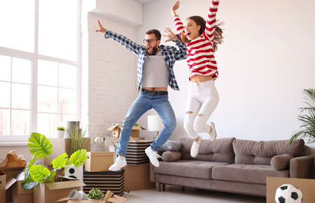 Full body of happy young family couple energetic couple having fun and jumping high while enjoying new home after relocation