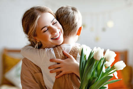 Happy woman with tulips smiling with closed eyes and embracing boy in gratitude while celebrating holiday at home