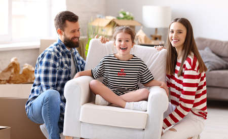 Cheerful man and woman smiling and lifting armchair with excited girl during relocation into new apartment 版權商用圖片