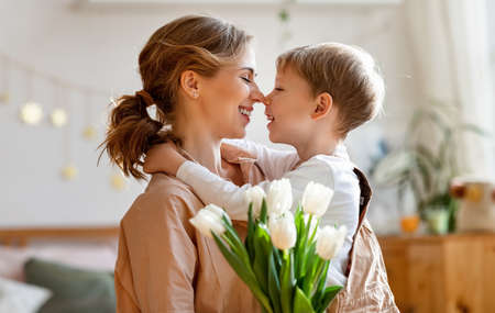 Optimistic mother with bouquet of white tulips smiling and touching noses with happy son while sitting on bed during holiday celebration at home