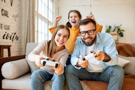 Cheerful family: girl raising arms and screaming while supporting mother and father sitting on sofa and playing videogame at home together
