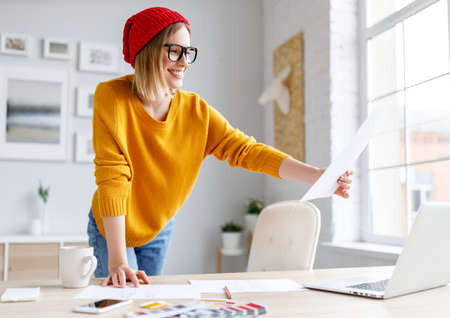 Cheerful female designer in stylish outfit and glasses smiling and drawing sketch during work on remote project at home