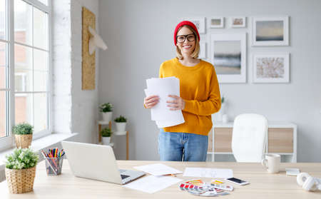 Cheerful female designer in stylish outfit and glasses smiling and holding documents on remote project while standing near table with computer at modern workplace at home