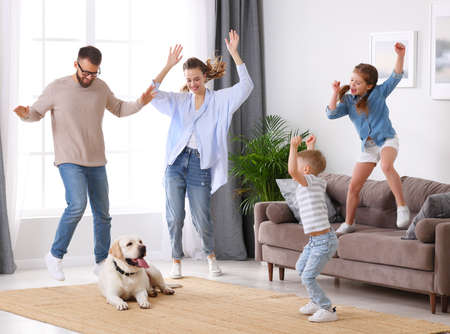 Full body of happy family: energetic parents and kids having fun and dancing while cute tired dog resting on carpet during weekend at home