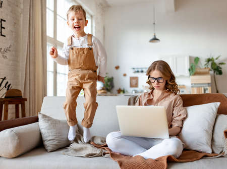 Tired young mother sitting on sofa and working with laptop while little son having fun, jumping and making noise