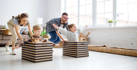 Playful family: parents riding kids in boxes and having fun during moving in new spacious apartment