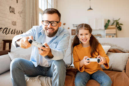 Happy family: bearded father and delighted daughter using gamepads to play videogame together while chilling on settee in weekend at home