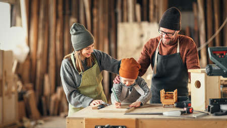 Excited little boy drawing sketch on wooden plank with help of father while spending day with parents in carpentry workshop