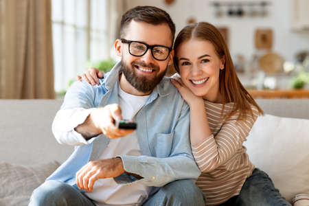 Delighted adult man and woman smiling and looking at camera while sitting on sofa and changing channels on TV with remote control