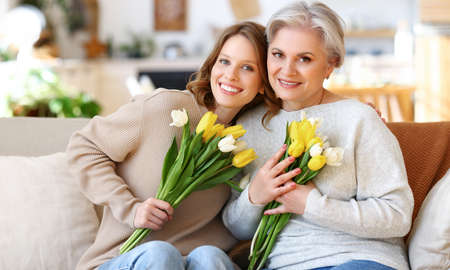 Positive young daughter with senior mother in casual clothes smiling and hugging while sitting on sofa at home with bunches of fresh delicate tulips during celebration of international Women Day