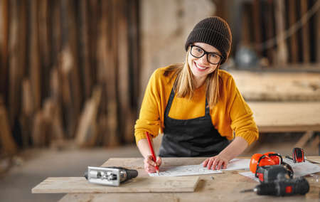 Cheerful young female carpenter looking at camera while checking documents and working in craft workshop
