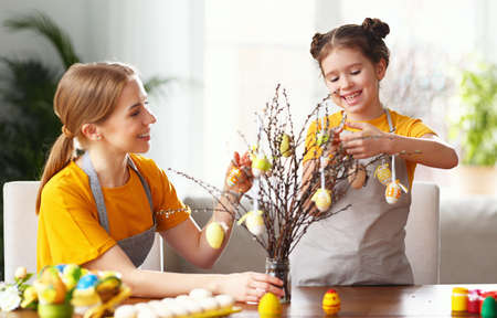 Smiling mother and cute daughter decorating willow branches with eggs at table while preparing for Easter celebration at home